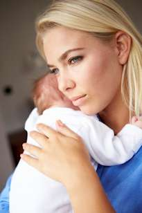 depressed mother cuddling newborn baby Postpartum Depression Treatment